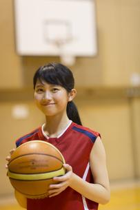 バスケットボールを持って微笑む女子学生の写真素材 [FYI02973038]