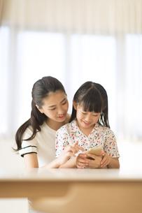 スマートフォンを見て楽しむ親子の写真素材 [FYI02973046]