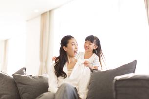ソファーに座って笑い合う親子の写真素材 [FYI02973052]
