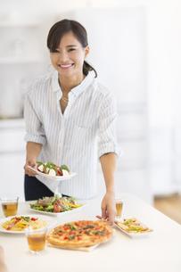 ダイニングテーブルで料理の準備をする女性の写真素材 [FYI02973053]