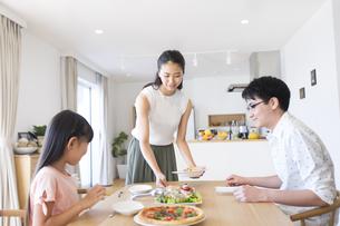 家族に食事を用意する母親の写真素材 [FYI02973054]