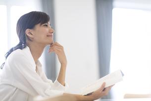 手に本を持ち微笑む女性の横顔の写真素材 [FYI02973067]