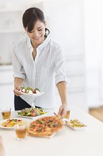 ダイニングテーブルで料理の準備をする女性の写真素材 [FYI02973068]