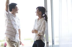 窓際で微笑み合う男性と女性の写真素材 [FYI02973079]