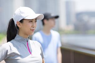 スポーツウエアを着て遠くを眺める男性と女性の写真素材 [FYI02973083]