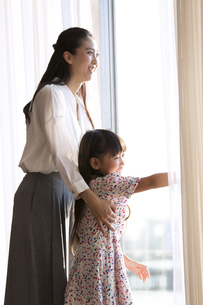 窓の外を眺める親子の写真素材 [FYI02973086]
