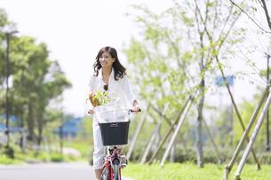 自転車で買い物をする女性の写真素材 [FYI02973089]