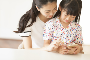 スマートフォンを見て楽しむ親子の写真素材 [FYI02973093]