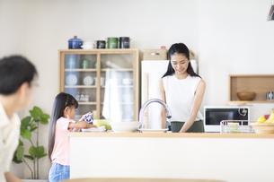 キッチンに立つ母親と手伝いをする子供の写真素材 [FYI02973097]