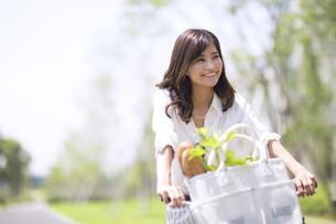 自転車で買い物をする女性の写真素材 [FYI02973099]