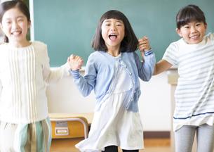 黒板の前で手を取り合って喜ぶ女の子たちの写真素材 [FYI02973112]