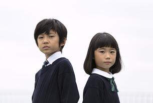 屋上に立つ小学生の男女のポートレートの写真素材 [FYI02973113]