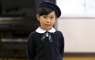 音楽室でピアノの前に立って微笑む女の子の写真素材 [FYI02973120]