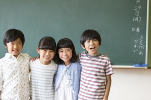 黒板の前で肩を組んで笑う子供たちの写真素材 [FYI02973121]