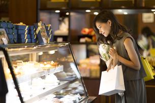 ショーウィンドウのケーキを選ぶ女性の写真素材 [FYI02973123]