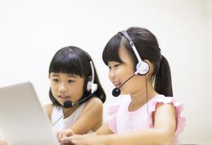 インカムを付けてパソコンを見る女の子2人の写真素材 [FYI02973127]