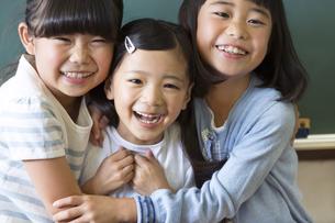 黒板の前で寄り添って笑う女の子3人の写真素材 [FYI02973129]