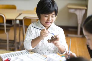 絵具の筆で色を塗る男の子の写真素材 [FYI02973133]