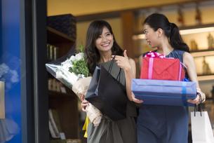 花束やプレゼントボックスを持って店を出る女性2人の写真素材 [FYI02973134]
