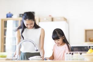 キッチンで食器を洗う親子の写真素材 [FYI02973141]