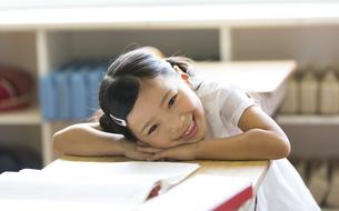 教室の机に寄り掛かって笑う女の子の写真素材 [FYI02973144]