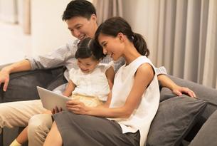ソファーでタブレットPCを見る家族の写真素材 [FYI02973145]