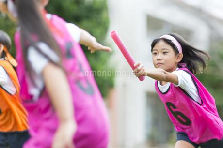 リレーのバトンを渡す女の子の写真素材 [FYI02973151]