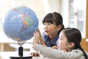 教室で地球儀を見る女の子2人の写真素材 [FYI02973157]