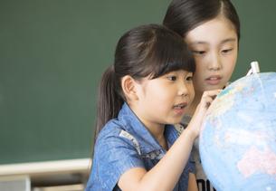 教室で地球儀を見る女の子2人の写真素材 [FYI02973164]