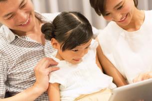 ソファーでタブレットPCを見る家族の写真素材 [FYI02973166]
