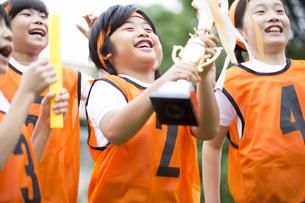 優勝カップを持って喜ぶ子供たちの写真素材 [FYI02973167]