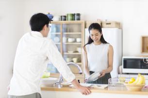 キッチンで食器を洗いながら男性と話す女性の写真素材 [FYI02973169]