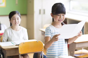 授業中に作文を読む小学生の女の子の写真素材 [FYI02973170]