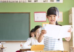 授業中に作文を読む小学生の女の子の写真素材 [FYI02973171]