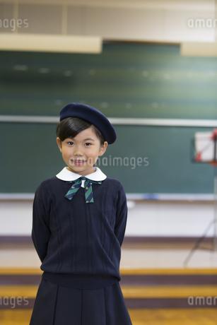 音楽室の教壇の前に立って微笑む女の子の写真素材 [FYI02973186]