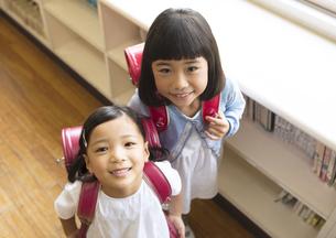 教室でランドセルを背負って微笑む女の子2人の写真素材 [FYI02973188]