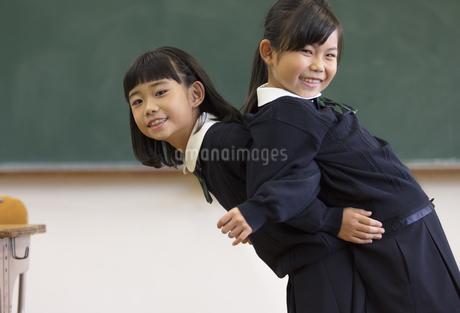 黒板の前で背中を合わせる小学生の女の子2人の写真素材 [FYI02973189]