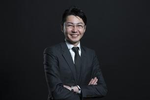 腕を組み微笑むビジネス男性の写真素材 [FYI02973190]