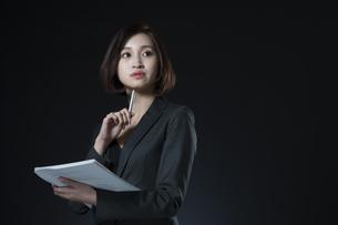 資料とペンを手に持つビジネス女性の写真素材 [FYI02973192]