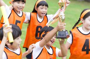 優勝カップを持って喜ぶ子供たちの写真素材 [FYI02973196]