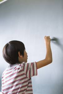 黒板に文字を書こうとする男の子の写真素材 [FYI02973199]