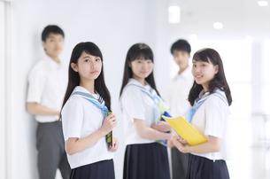 学校の廊下で教材を持って微笑む女子学生3人の写真素材 [FYI02973200]