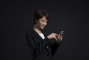 スマートフォンを操作するビジネス女性の写真素材 [FYI02973202]