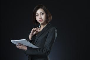 資料とペンを手に持つビジネス女性の写真素材 [FYI02973204]