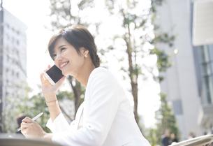 スマートフォンで通話するビジネス女性の写真素材 [FYI02973206]