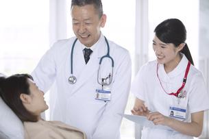入院患者を診察する男性医師と女性看護師の写真素材 [FYI02973215]