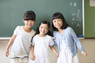 黒板の前に並んで立って笑う女の子3人の写真素材 [FYI02973217]