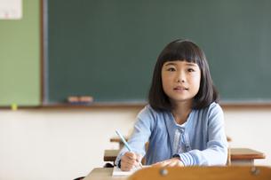 教室の椅子に座って勉強をする小学生の女の子の写真素材 [FYI02973226]
