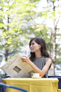 オープンカフェで新聞を持つ女性の写真素材 [FYI02973228]