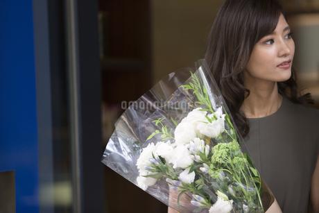 花束を持って遠くを見る女性の写真素材 [FYI02973232]